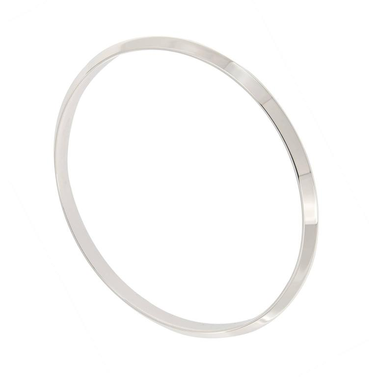 Signature style bangle bracelets from Tiffany. This bracelet is simple and classic on its own or great for stacking. We have five available.   Inner Diameter 2.5 in. (6.35 cm). Weighs 17.1 grams.  Marked Tiffany & Co.