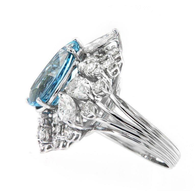 Be prepared for compliments with this exceptional cocktail Ring. Ring centers around a stunning 5.27 carat pear shaped aquamarine of intense sky blue color, the quintessential color of the finest aquamarine. Auqamarine is surrounded by a cluster of