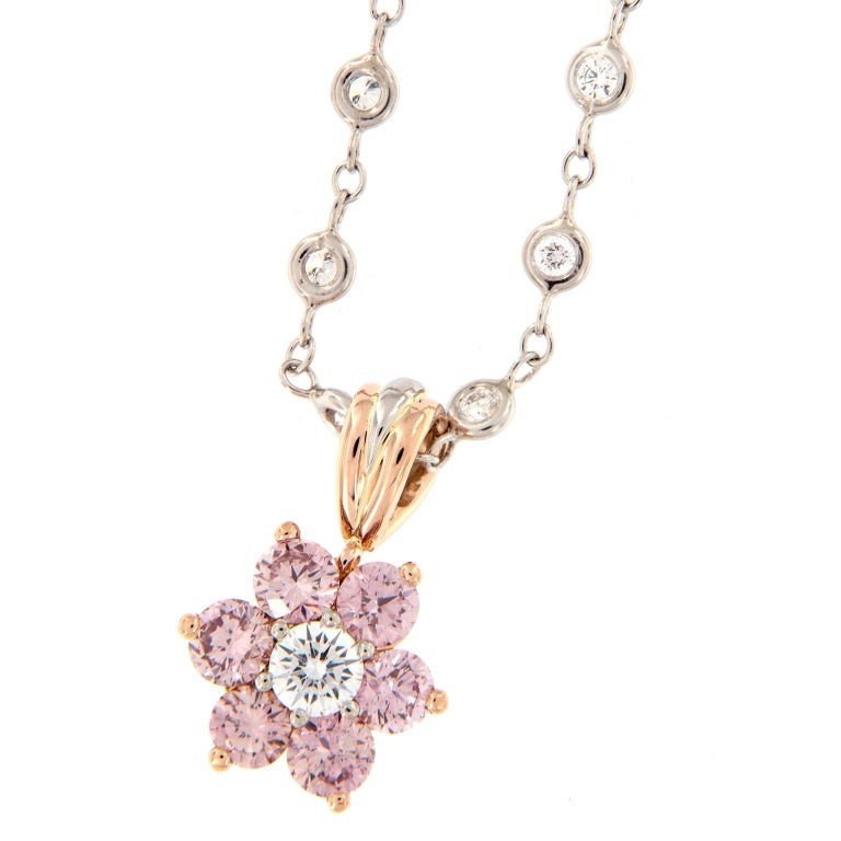 Gorgeous floral cluster pendant centers around a round brilliant-cut white diamond framed by six round brilliant-cut fancy pink diamonds in 18k rose gold and platinum. Pendant hangs from an outstanding hand-fabricated 16.25 inch platinum chain