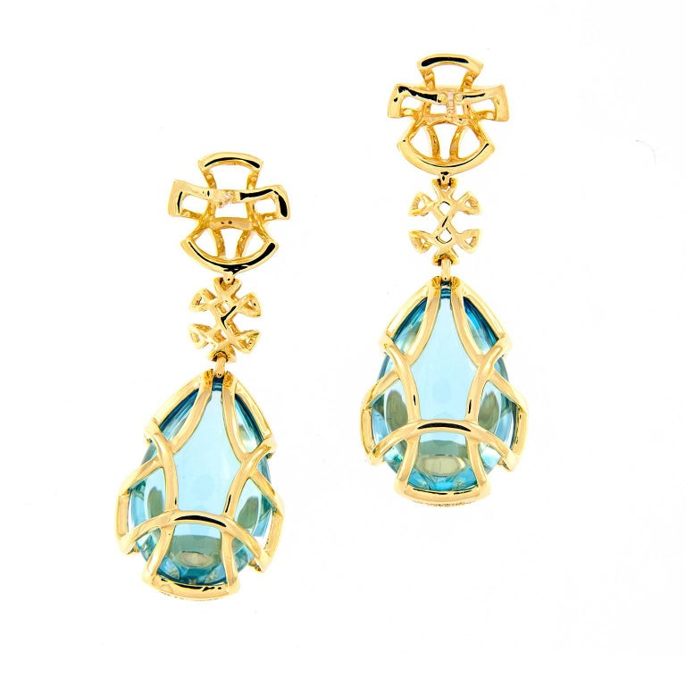 These blue topaz teardrops drop from double 18k yellow gold discs and are covered in a gold cage design. From the Freedom Collection designed by Goshwara. Weighs 20.8 grams. Marked Goshwara.  Blue Topaz 18.08 cttw