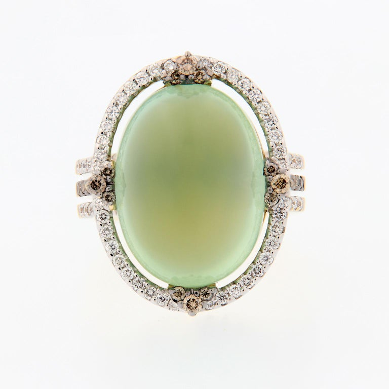 Prehnite is an intriguing gemstone that features a unique green glow. This ring centers around a 16.92 carat cabochon cut prehnite, accented with white and champagne colored diamonds. Ring size 6.5. Weighs 12.5 grams.  Prehnite 16.92 ct Diamonds