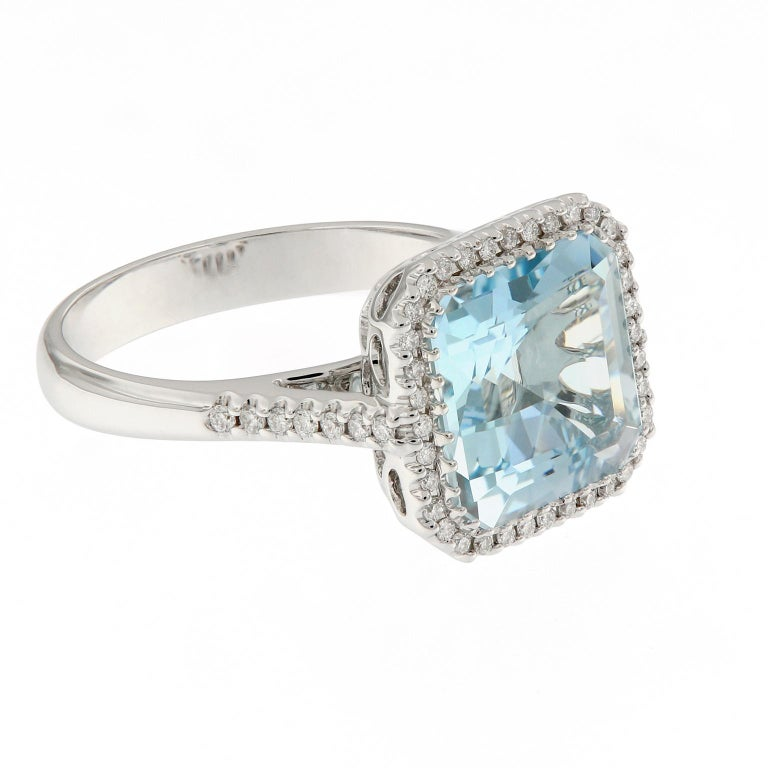 This gorgeous 18k white gold cocktail ring features a square step-cut aquamarine surrounded by a halo of pavé-set diamonds and beautifully balanced with diamonds running down the shank. Ring size 6.5. Weighs 5.2 grams.  Aquamarine 3.63 ct Diamonds