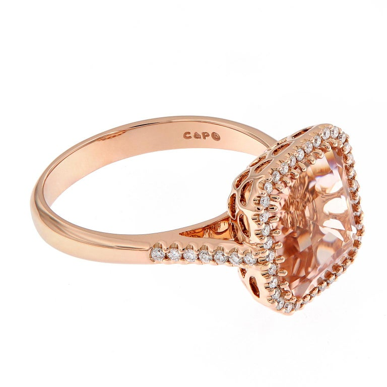 Beautiful 18k rose gold cocktail ring centers around a 3.79 carat morganite, surrounded with a halo of diamonds and beautifully balanced with diamonds running down the shank. Ring Size 7. Weighs 5 grams.  Morganite 3.79 ct Diamonds 0.26 cttw