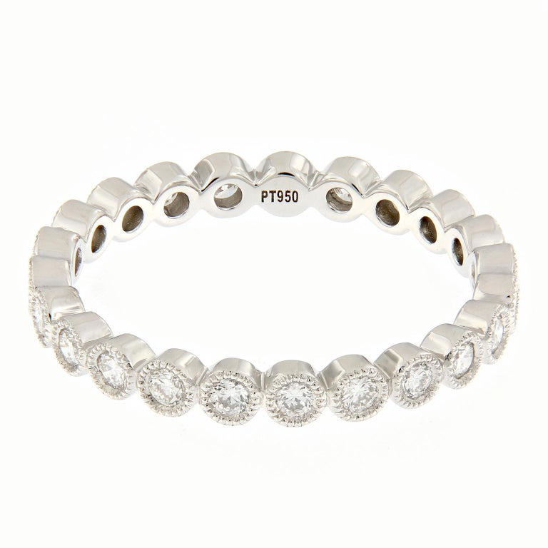 This eye-catching diamond eternity band features 23 round brilliant cut diamonds set into individual bezels edged with milgrain. Perfect for a wedding band, to stack or wear on its own. Weighs 2.6 grams. Ring size 7.  Diamonds 0.54 cttw