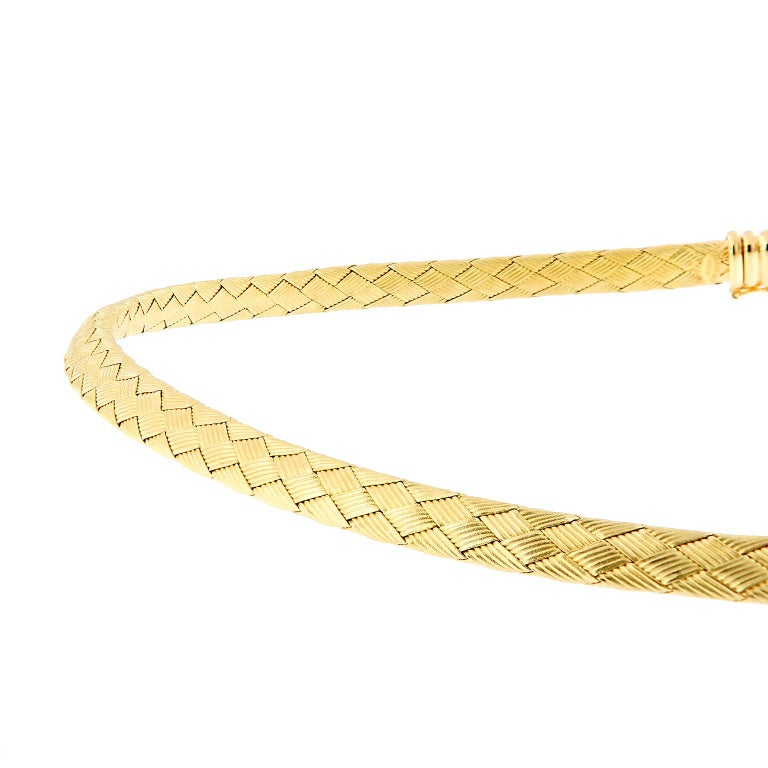 This beautiful Italian necklace is done with woven textured sheets of 18k yellow gold creating a basket-like weave design. The finish is softwith a smooth feel on the skin. This Omega style necklace is 16 inches long and features a safety clasp that