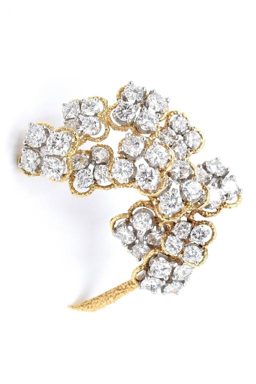 Elegant Van Cleef & Arpels Floral Diamond  Brooch 41 large brilliant diamonds set in platinum surrounded by rope design leaves 18k gold Estimated total weight of diamonds is 10 carats  Color F/G Clarity VVS2 Measurement: 1.7