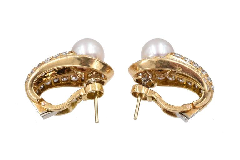 Cartier, France. Pair of Gold, Cultured Pearl and Diamond Earrings,  The rounded tapered panels centering 2 pearls approximately 8.0 mm., set with 74 round diamonds approximately 3.45ct. Measure 7/8 x 9/16 inch. Have posts & clip-backs.  Signed
