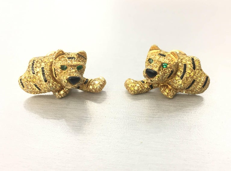 Adorable! Yellow and White Diamond Tiger Earrings. Diamonds estimated to weigh a total of approximately 8 carats, of various tints. Emerald eyes, onyx stripes and nose. Measurements: 30 by 18mm Gold weight: 18.30dwt  French maker's marks and French