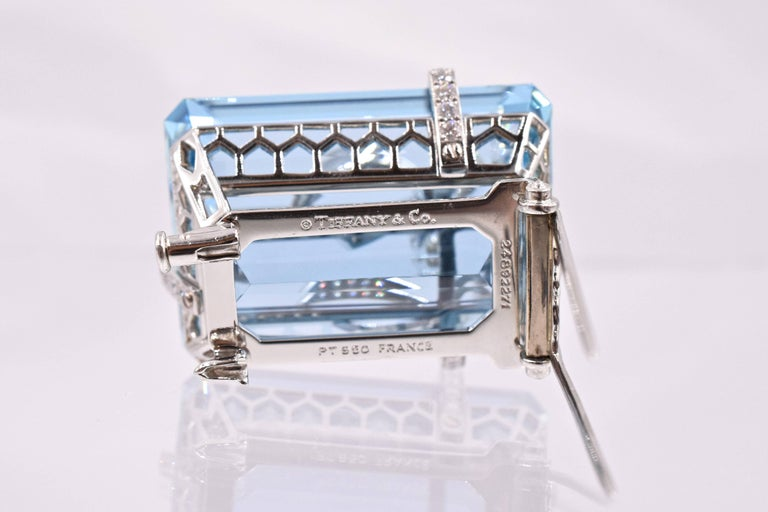 An Aquamarine and Diamond Brooch, by Tiffany and  Co. Set with a rectangular-cut aquamarine, weighing approximately 91.03 carats, wrapped with a circular-cut diamond ribbon and bow,  Measurement is1 ⅜ ins    mounted in platinum.  Signed Tiffany and