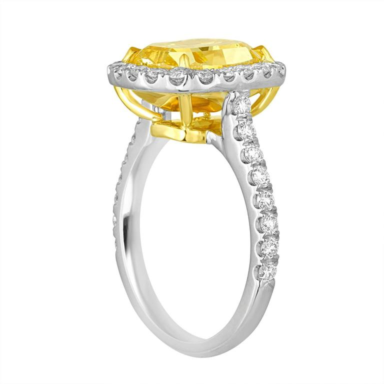 4.76 Carat Cushion Shaped Diamond is GIA certified as Fancy Vivid Yellow in Color and SI2 in Clarity. The Diamond is full of life and beauty. The Cushion is set in Two Tone Mounting with 70 Brilliant 1.54 Carat Total Weight in Halo settings. White