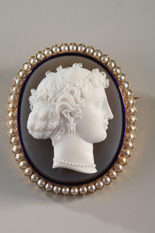 Large and exceptional cameo in two com or agate, circled with blue enamel and natural pearls. Mounted as a brooch in yellow  gold. Admire the delicacy of execution and the beauty of the profile. In its original box.
