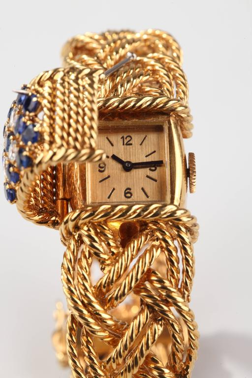 Boucheron Paris Formed of twisted yellow gold rope centered by a motif set with brillant cut diamonds and round blue sapphires, hiding a yellow gold watch. Mechanical movement. French assay marks for gold. Signed and numbered .