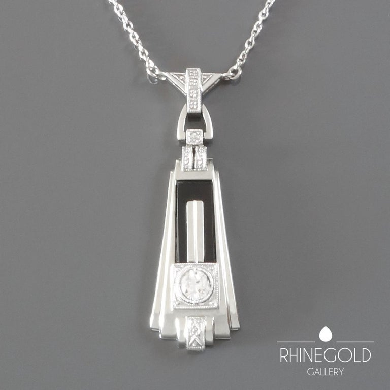 "1920s German Art Deco Diamond Onyx White Gold Pendant Necklace 18k white gold (pendant), 14k white gold (chain), old European cut diamond (approx. 0.2 carat; H; vvs2), onyx Pendant 3.5 cm by 1.1 cm (approx. 1 3/8"" by 7/16""); chain 42.3 cm (approx."