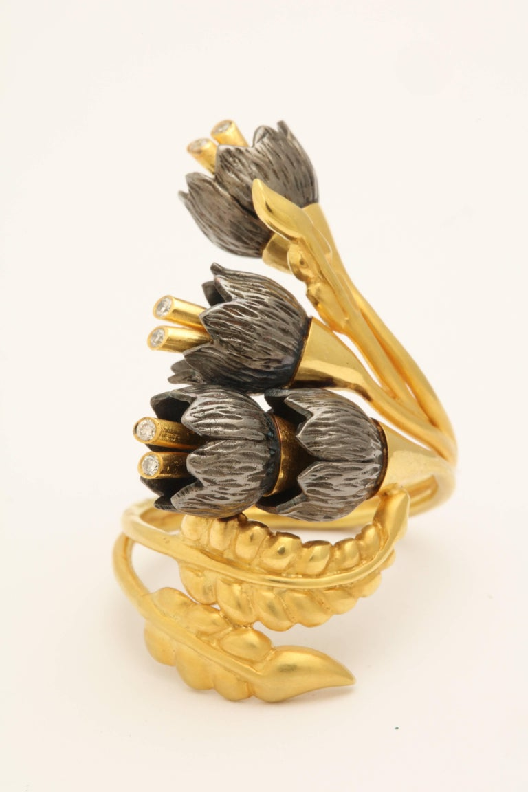 A lily of the valley ring composed of 18kt yellow gold leaves and four rhodium plated sterling silver lily of the valley flowers. The flowers cascade down an 18kt yellow gold vine. Each flower has 18kt yellow gold stamen set with diamonds. Size