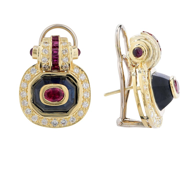 Striking modern design earrings featuring 2 oval cut and 20 calibre cut rubies, 2 fancy cut sapphires, and  50 round brilliant cut diamonds with an estimated total weight of 1 carat.   Metal Type: 18 Karat Yellow Gold Metal Weight: 16.8 Grams