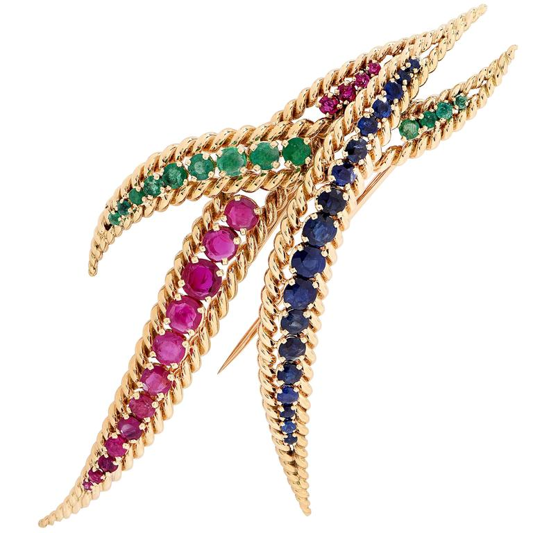 Large Mauboussin brooch set with 13 emeralds weighing approximately 1 carat, 18 sapphires weighing approximately 3 carats and 16 rubies weighing approximately 3.50 carats. Numbered and signed Mauboussin Paris.   Metal Type: 18Kt Yellow Gold Metal