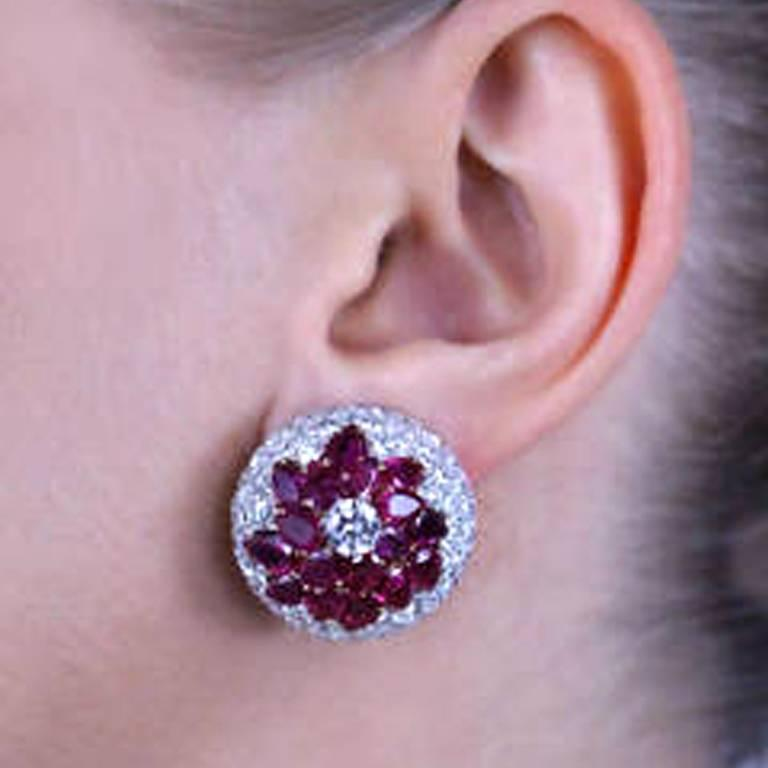 These magnificent Burmese Ruby and Diamond earrings feature approximately 12 carats of pear shaped vibrant red rubies surrounded by 9 carats of fine quality diamonds E/F color and VS/SI clarity set in platinum with 18 karat white and yellow gold