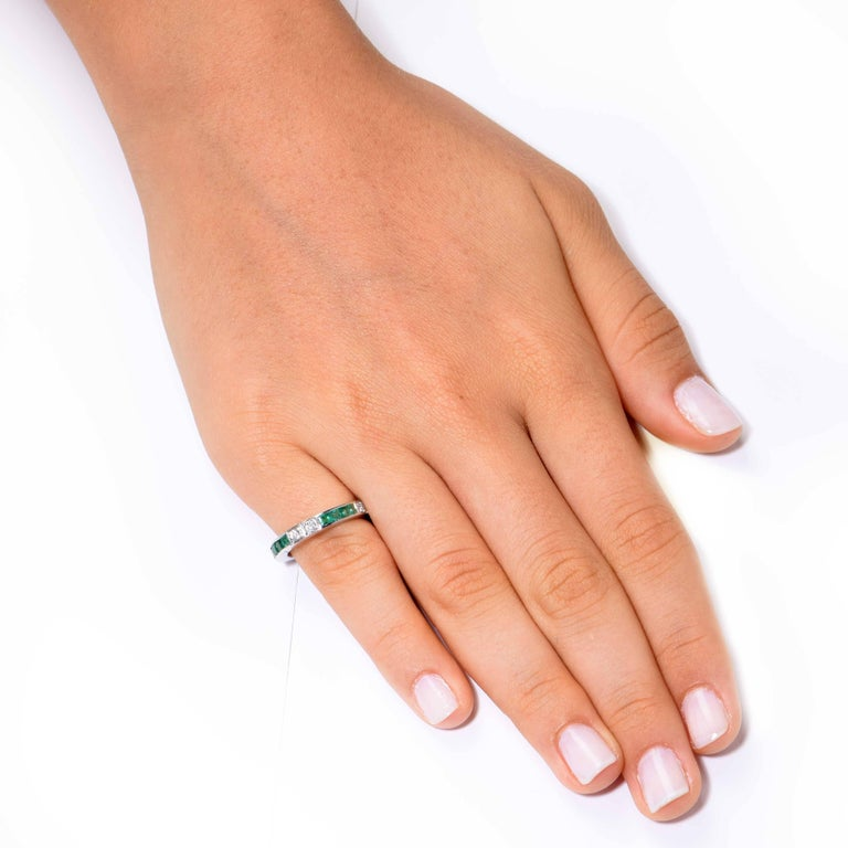 This trendy Emerald and Diamond Band features 16 square cut emeralds and 8 round cut diamonds. The emeralds have an approximate total weight of 1.2 carats and the diamonds have an approximate weight of .40 Carats.  Ring Size: 5 3/4 (cannot be