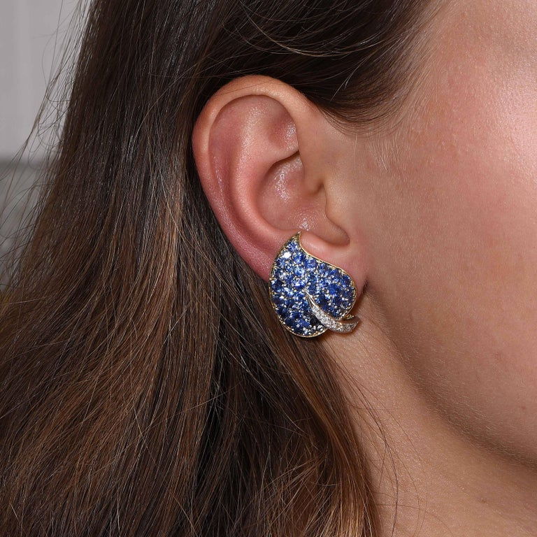 Sapphire and Diamond Van Cleef and Arpels leaf design earrings featuring 56 round cut blue sapphires with an estimated total weight of 5.6 carats and 14 transitional cut diamonds with an estimated total weight of .45 carats set in 18 karat yellow