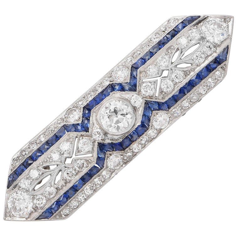 Art deco platinum, sapphire and diamond brooch bezel set with and old european cut diamond and set throughout with old european and old single cut diamonds with an with millegrain accents weighing approximately 2.10 carats and 2 rows of calibre-cut