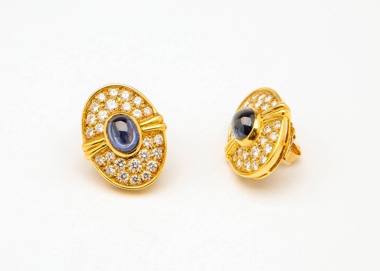 Beautiful cabochon sapphires are surrounded with brilliant cut diamonds and framed by rich 18k yellow gold. Iconic jeweler Harry Winston creates wearable style. Sapphires 3.00ct total weight and diamonds 1.50ct total weight. 1 inch in size.