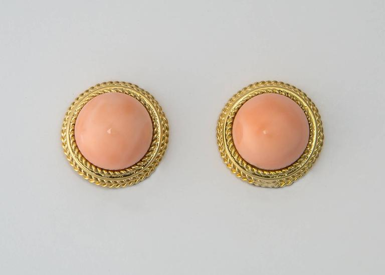 The color and tone of angel skin coral is beautiful and flattering for any complexion. Perfectly matched coral is firamed with rich 18k gold.  7/8's of an inch in size.
