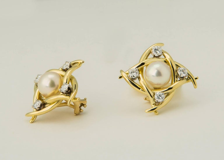Classic Tiffany style and quality. A lustrous 8.00mm pearl is framed by elegant ribbons of 18k gold and finished with brilliant cut diamonds. 7/8's of an inch in size. .96 carats total diamond weight.