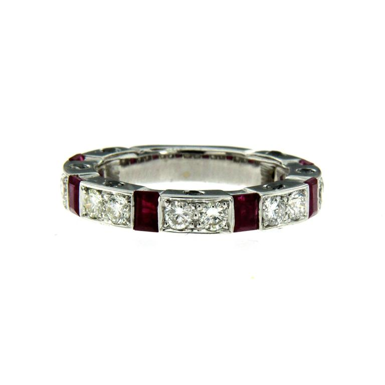 This stunning white gold band ring features round brilliant cut diamonds with a total weight of 1.12 carats G color VVS, 6 rubies weighing totally 0.70 cts and 0.42 cts of black diamonds adorning both sides.   CONDITION: Brand New METAL: 18k