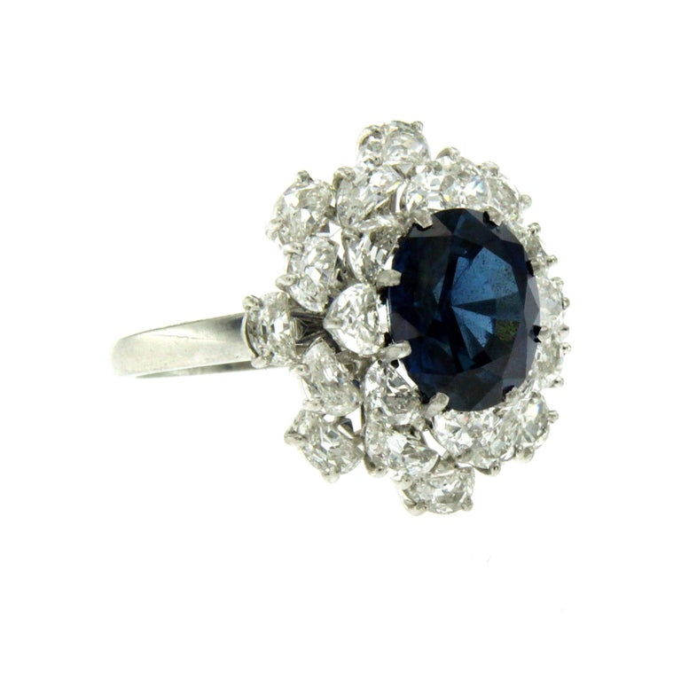 Platinum, Sapphire and Diamond Ring, set in the center with an oval-cut Sapphire weighing 3.40 carats framed by a double halo consisting of 3.50 carat of half moon cut diamonds graded H color and Vvs clarity. Circa 1980  CONDITION: Pre-owned -