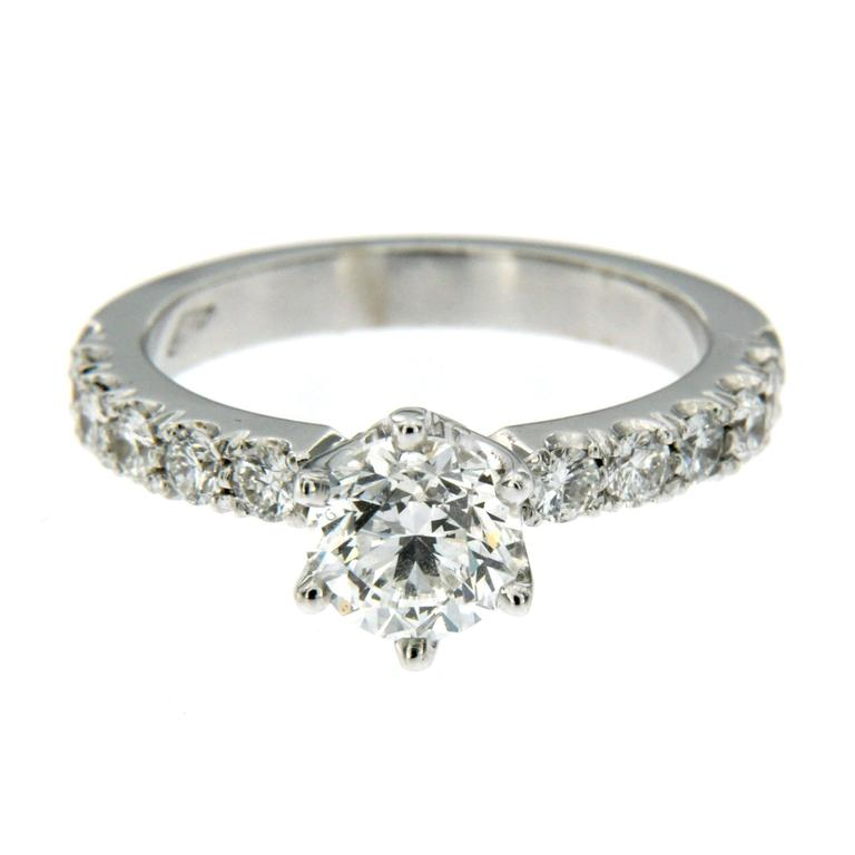 18k Gold Engagement ring consisting of 1 round cut center diamond grades F color and VS2 clarity, weighing 1ct with IGI Report 208600378 and 10 full cut round diamonds set on the shoulders having a total weight of 0.60 ct Diamond measurements: 5.97