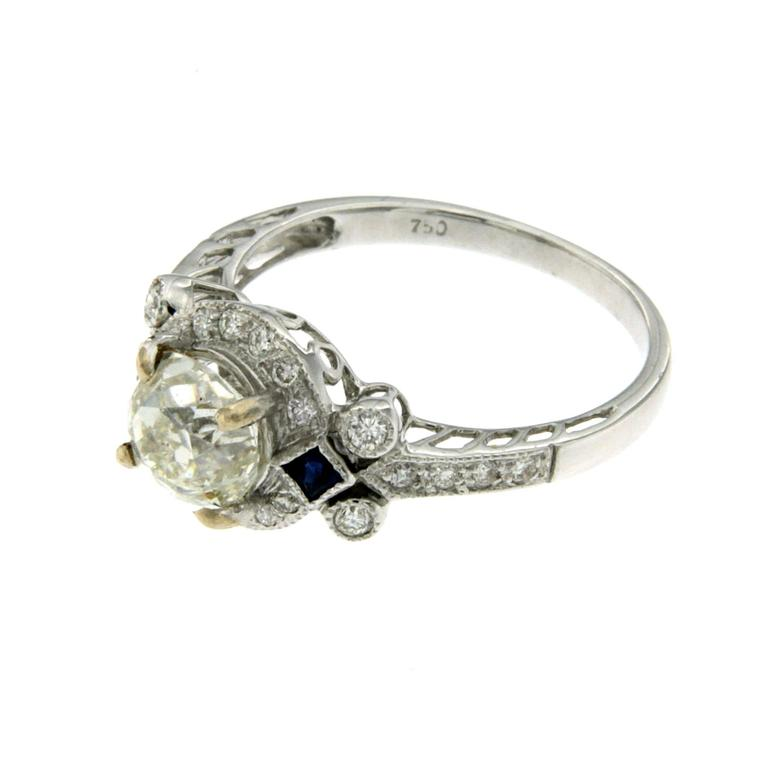 An Antique Art Deco 18k Gold Diamond & Sapphire Ring featuring a stunning 1.36ct. old mine cut Diamond with VS2 Clarity I Color, surrounded by 24 diamonds 0.26ct. Clarity VS Color G. There are also two 0.10 carat briolette cut Sapphires flanking the