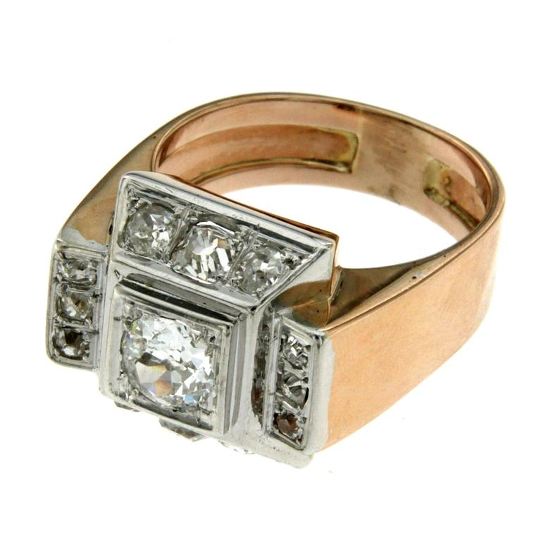 This 18k white and rose Gold band ring is set in the center with an european-cut diamond weighing 1.00 carat color H clarity VS1 flanked by 12 european-cut diamonds for a tot. weight of 1.10 carat graded H VS1.