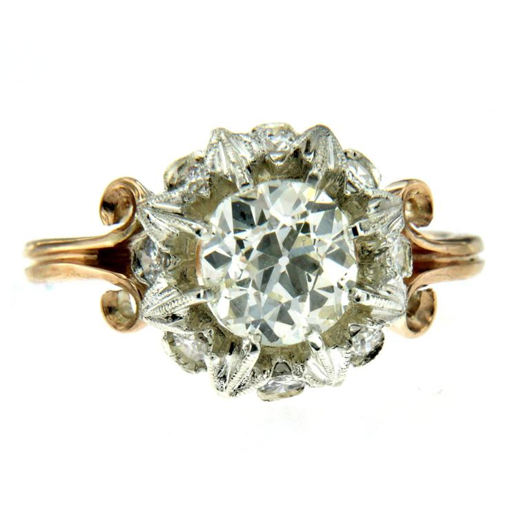 A beautiful original and unique Art Noveau diamond engagement ring set in 18K yellow and white gold hand worked into a gorgeous blooming flower. The ring features a center 1.40 carat old mine cut diamond M color Vvs, 