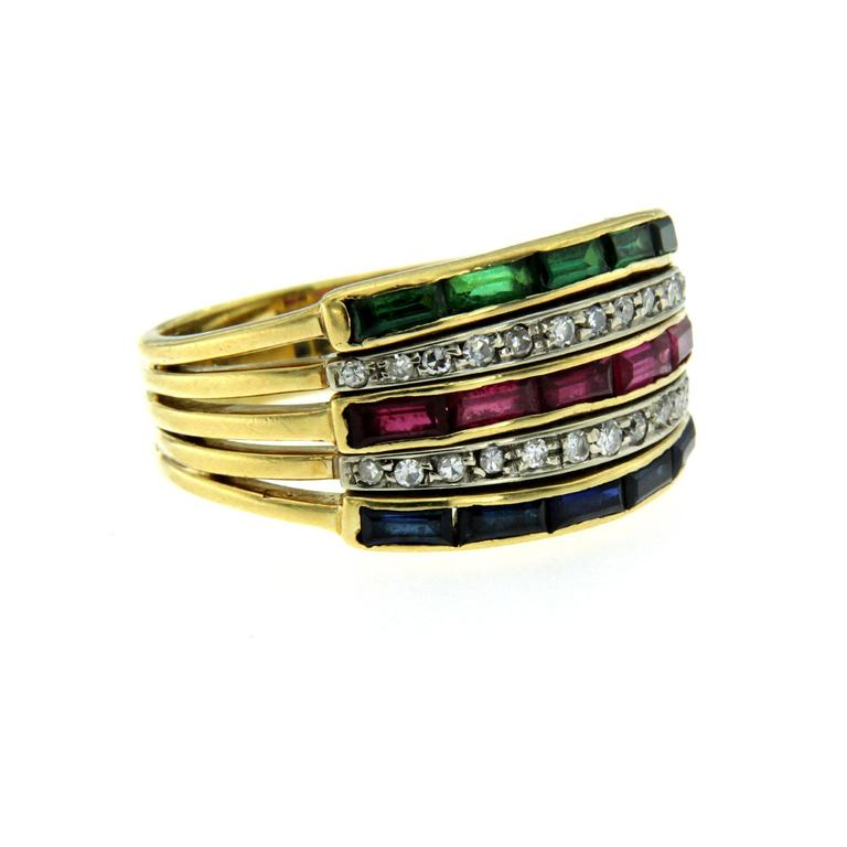 Diamonds, rubies, emeralds and blue sapphires 18k yellow gold band ring. The diamonds have a total weight of 0.30, which contrast beautifully with the 1.50 total carats of baguette cut rubies, emerald and sapphiress. Circa 1950  CONDITION: Pre-owned