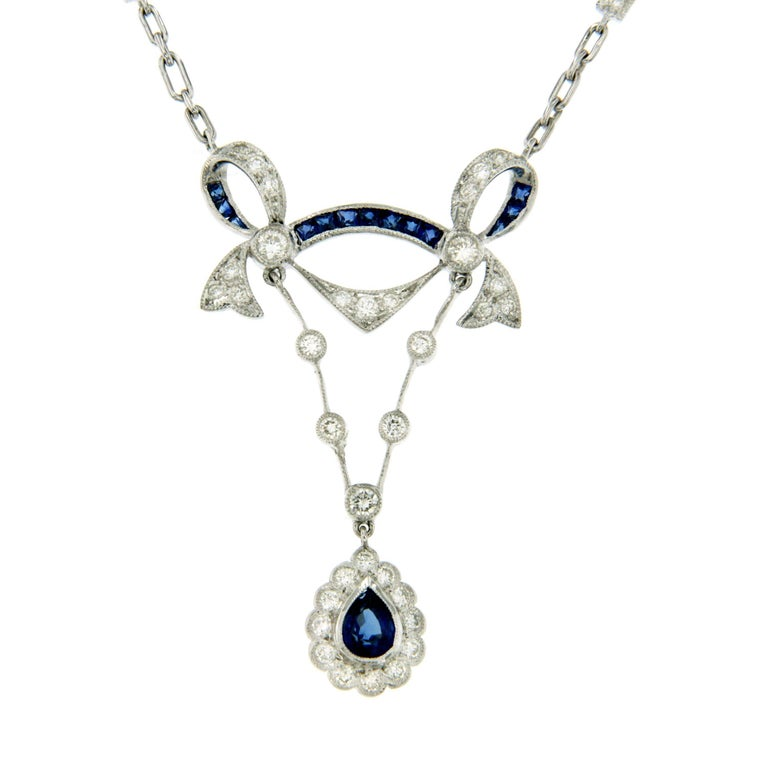 Cluster pendant, featuring a pear-shaped sapphire framed by round brilliant cut diamonds suspended on a gold chain adorned by diamonds and sapphires.  Sapphires weighing approximately 1 ct and diamonds weighing approximately 0.60 total