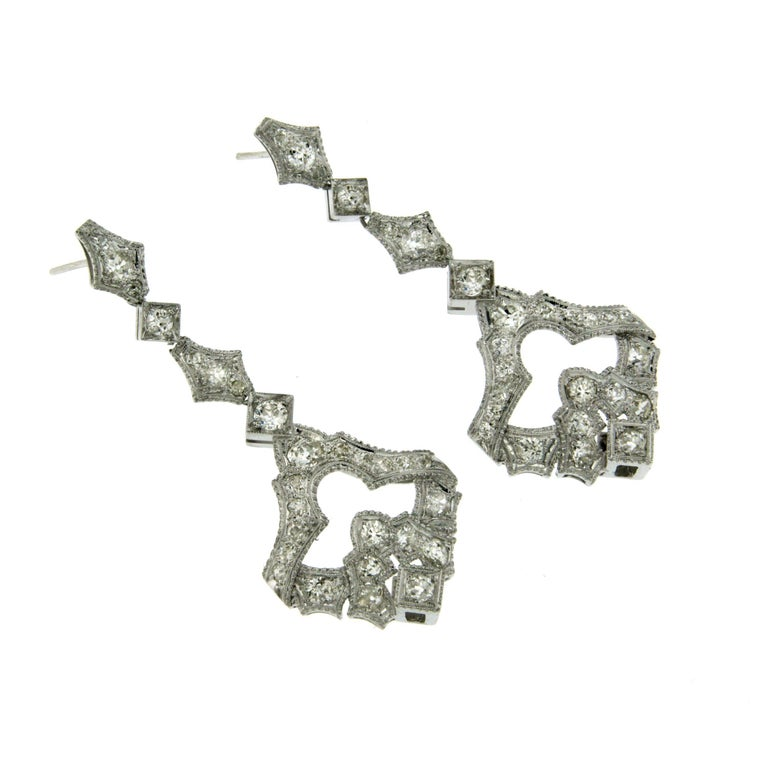 This elegant pair of diamond 18k white gold earrings feature sparkling round brilliant cut diamonds that weigh approximately 5.50ct. graded G-H color with VS clarity. Circa 1930  CONDITION: Pre-owned - Excellent  METAL: 18k white Gold  STONE: