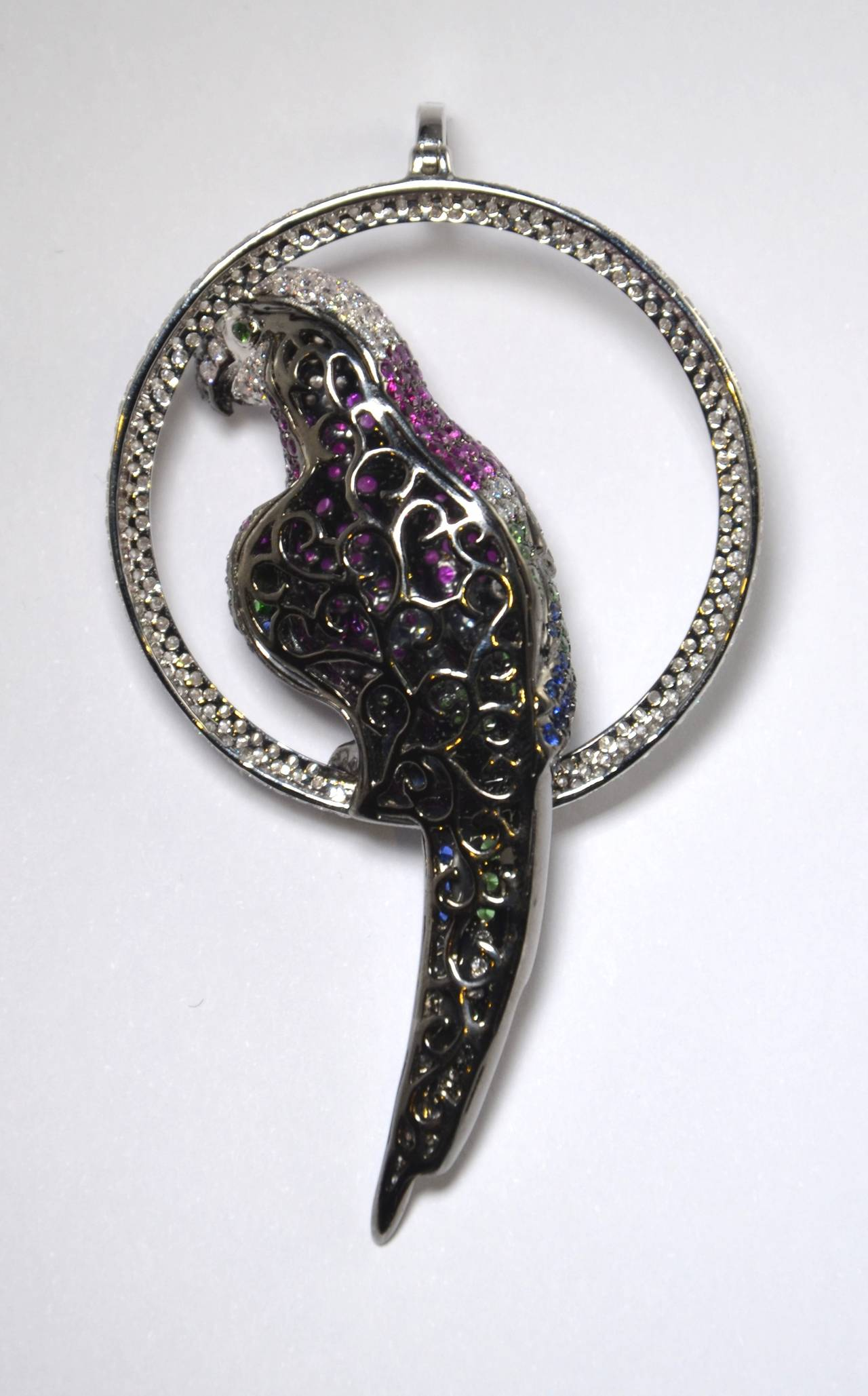 A rare and beautiful parrot in a circle pendant. Diamonds, pink and blue Sapphires and Tsavorite Garnets mounted in 750/White gold partly with a black rhodium finish.    Brillant-Cut Diamonds of approx. 3.68 ct., TW/vsi,   Black Diamonds, of