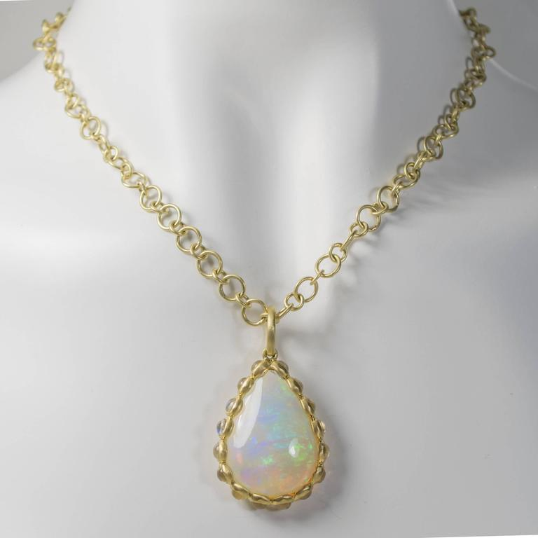 Be prepared for swooning glances with this incredible, one-of-a-kind Ethiopian opal and moonstone pendant.  The handmade setting is 18k green* gold featuring a 9.13 cts. pear-shaped opal surrounded by 16 bezel set moonstones.  Incredible color in a