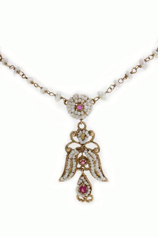 Delicate necklace in 12kt rose gold composed of a micropearls chain with rubies and pearls which shapes flowers and on the bottom a micropearls and rubies pierced pendant. pearls( total weight 5.10 gr )   rubies ( total weight 0.23 kt) . Total