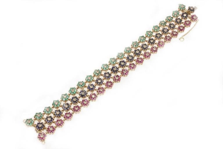 Colored bracelet in 14Kt gold composed of three single strands of  emeralds, rubies, blue sapphires. emeralds, rubies, blue sapphires (tot weight 21.41Kt)  diamonds(1.90Kt),   Tot weight 35gr Rf. ggchh  For any enquires, please contact the seller