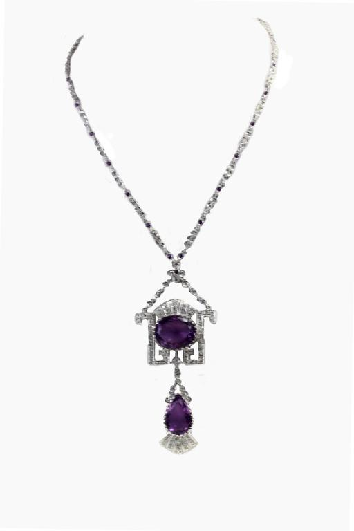 Shiny pendant necklace in 14kt white gold all covered in diamonds embellished with amethist on the chain and two bigger amethyst on the pendant. amethyst 38/39 kt diamonds 4.44kt tot weight 44.7gr r.f.   gohfu
