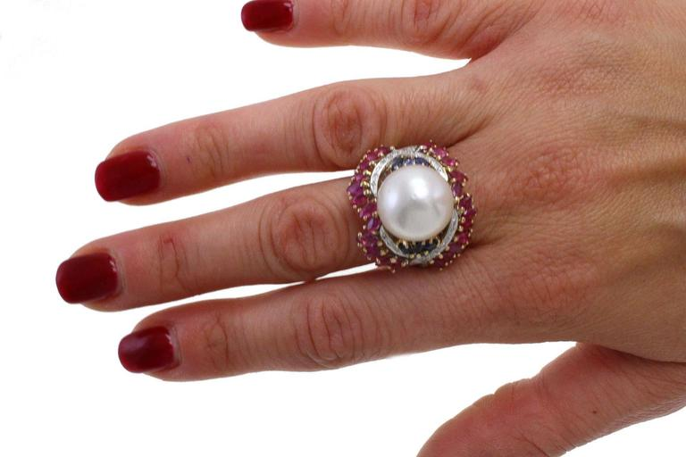 Precious ring in 14kt white and yellow gold composed of a central big australian pearls surroundes by a crown of diamonds, rubies and blue sapphire.  diamonds 0.42kt rubies, blue sapphire 2.71kt pearl 3.80 gr tot weight 10.5gr US Size Width 0.79
