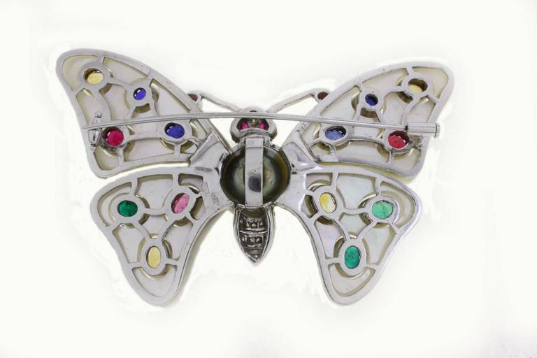 Graceful butterfly shaped brooch in14K white gold composed of mother of pearl wings with details of pink, blue, yellow, green sapphires. The body is covered in diamonds and also there is a large pearl in the middle to connect all.   mother of pearl
