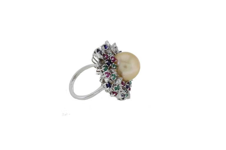 Cluster ring in 14k white gold mounted with one yellow south sea pearl in the center and diamonds, emeralds, rubies, blue sapphires all around it. Diamonds 1.55 kt Emeralds, Rubies, Blue Sapphires 3.38 kt Pearl 3.60 gr/ 13.50 mm Tot.Weight 14.50