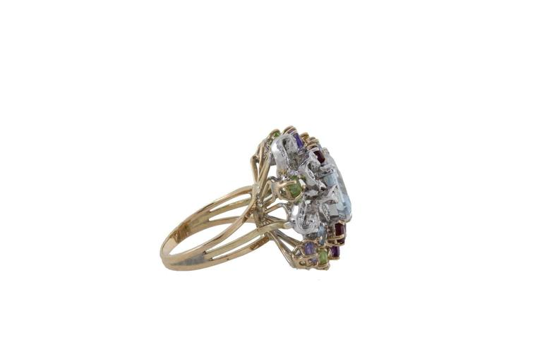 Cluster ring in 14k yellow and white gold mounted with aquamarine in the center and diamonds topaz peridots amethysts tanzanite garnets aquamarine around. Diamonds 0.58 kt Topaz Peridots Amethysts Tanzanite Garnets 3.32 kt Aquamarine 4.05