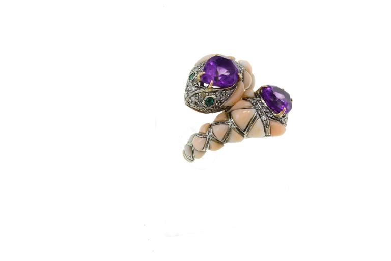Snake ring in 9Kt gold  and silver adorned with a central amethyst on the head  surrounded by diamonds and coral on the body. It presents shiny emeralds as eyes.  amethyst (6.25Kt)  diamonds(1.40Kt)  coral(1.70gr) emeralds (0.23Kt) Tot weight 15.4