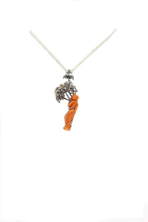 Elegant brooch/pendant in 9Kt white gold and silver. is a coral lady figurine that holds a palm adorned with diamonds  and blue sapphires. coral (5.50gr) diamonds (0.33Kt)   blue sapphires(0.35Kt) Tot weight 15.4gr R.f.514209 For any enquires,