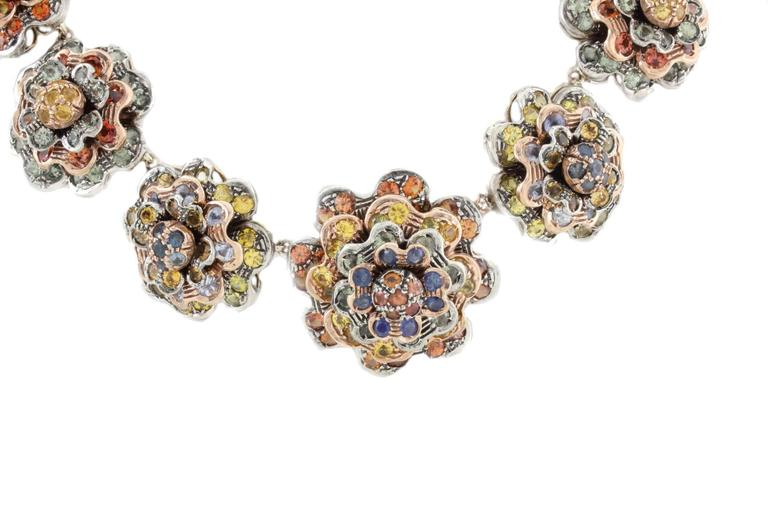 This fashion design flowers choker necklace it is mounted in 9Kt rose gold and silver. All the flowers are composed of multi colored sapphires (77.22Kt) Tot weight 156.1 gr R.f 962541