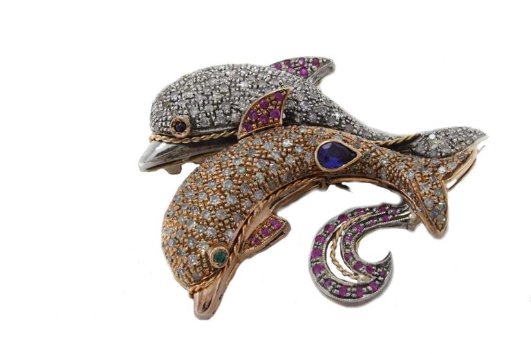 These lovely dolphins are mounted in 14Kt rose gold and silver.  Dolphins's bodies are embellished with diamonds(3.60Kt) blue sapphires and rubies(1.25Kt). tot weight 18 gr R.f. 140487  For any enquires, please contact the seller through the message