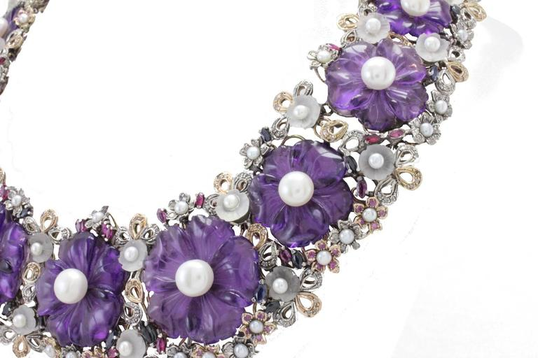 Charming and fashion design necklace, composed of flower shape amethyst and  rock crystal  (54.1Kt) with a diameter between 3-7mm(13.20,  diamonds(5.66Kt) and emeralds, rubies, and blue saphires(14.55Kt). All mounted on 9Kt gold and silver. Tot
